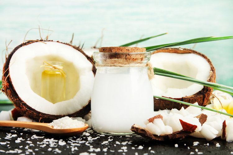Coconut milk glass jar with nuts and oil bottles, fresh coconut flakes.