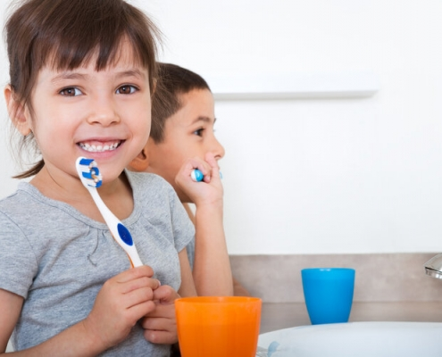 Sibling brushing teeth together