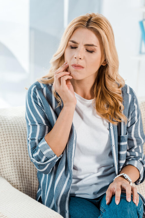 woman with closed eyes having toothache while sitting on sofa